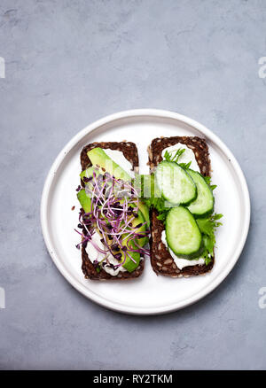 rye bread with avocado, cream cheese, cucumber, sprouts in a white plate on a gray background - Stock Image