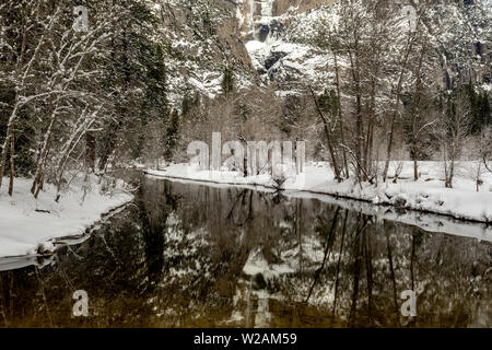 A view of Yosemite Merced River and Falls from the valley, in the winter, featuring accumulated snow, California, USA, with reflections in the water - Stock Image