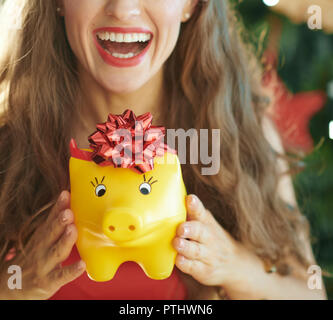 smiling modern woman showing yellow piggy bank with red bow near Christmas tree - Stock Image