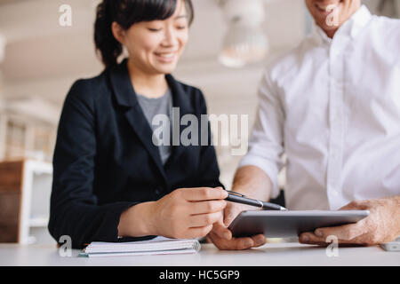 Two young business people working together, with female executive pointing digital tablet. Businessman and businesswoman - Stock Image