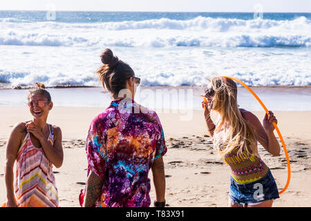 Cheerful happy people caucasian group enjoy the summer holiday vacation at the beach having fun together in friendship - coloured clothes and sea in b - Stock Image