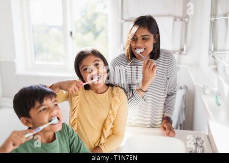 Portrait happy family brushing teeth in bathroom - Stock Image