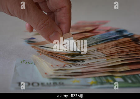 Concept : business and finance. Hand and pile of euros - Stock Image