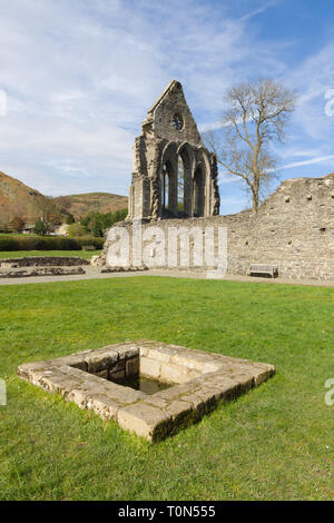 The ruins of Valle Crucis Abbey with the well in the foreground. Founded as a Cistercian monastery in 1201 and closed in 1537 - Stock Image