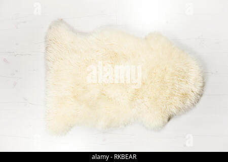 Flat lay view of white warm and cozy whole real decorative sheepskin rug on white wooden board floor.  Room for text. Studio set. - Stock Image