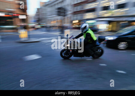 motorcyclist riding motorbike around corner motion blur, London, England, UK - Stock Image