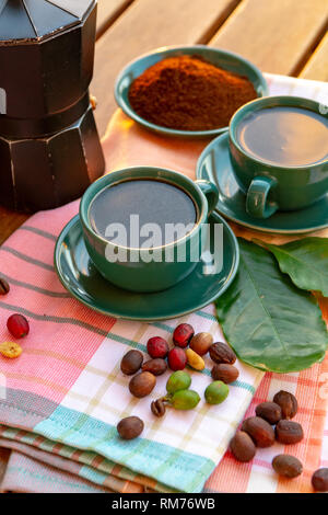 Cup with black coffee served outside with raw green, mature red and roasted coffee beans, decorated with green leaves from coffee plant close up - Stock Image
