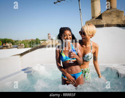 Portrait laughing, carefree young women friends drinking champagne in sunny rooftop hot tub - Stock Image
