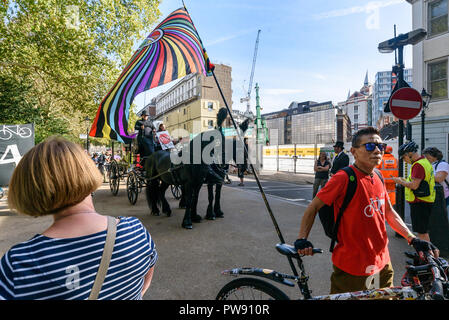 London, UK. 13th October 2018. People wait for the start of the funeral procession of cyclists behind a horse-drawn hearse to highlight the failure of governments from all the major parties to take comprehensive action on safer cycling. Stop Killing Cyclists call for £3 billion a year to be invested in a national protected cycling network and for urgent action to reduce the toxic air pollution from diesel and petrol vehicles which kills tens of thousands of people every year, and disables hundreds of thousands. The several hundred protesters staged a ten-minute die-in outside Parliament before - Stock Image