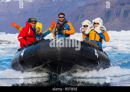 Greenland, Scoresby Sund, Gasefjord. Expedition staff bring hot cocoa to tourists in zodiac boats. - Stock Image