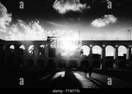 19th-century colonial Lapa Arches, Rio de Janeiro, Brazil - backlit with sun rays coming through one of the openings - monochrome - Stock Image