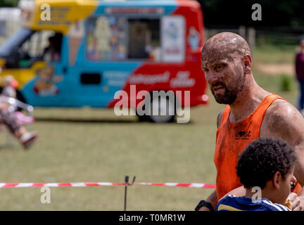 Shaven headed man at the end of a mud run - Stock Image