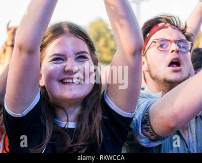 A young excited female fan with glitter and a big smile on her face in the front row of the Obelisk Stage at Latitude Festival 2018. - Stock Image
