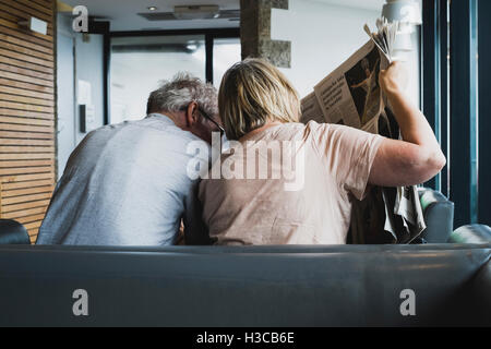 A couple reading a broadsheet newspaper at Gylly Beach Cafe, Gyllyngvase beach, Falmouth, Cornwall - Stock Image