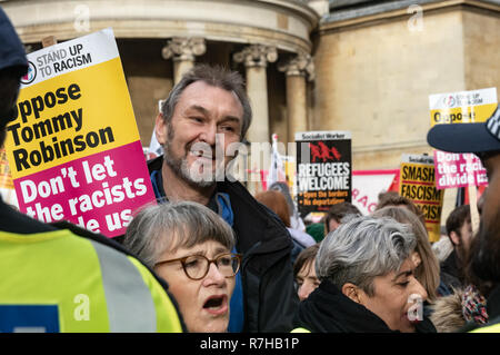 London, UK. 9th Dec, 2018. Protesters line up close to the BBC for the united counter demonstration by anti-fascists marches in opposition to Tommy Robinson's fascist pro-Brexit march. NEU General Secretary Kevin Courtney and Nita Sanghera of UCU at right. The march which included both remain and leave supporting anti-fascists gathered at the BBC to to to a rally at Downing St. Police had issued conditions on both events designed to keep the two groups well apart. Credit: Peter Marshall/Alamy Live News - Stock Image