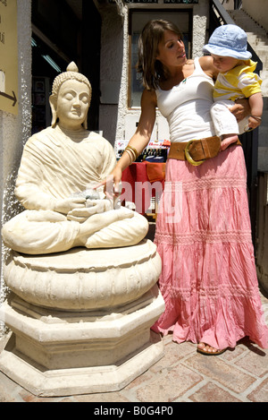 Mother and toddler pointing at a Buddha statue outside a craft shop in Mijas Pueblo, Costa del Sol, Andalucia, Spain - Stock Image