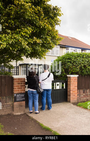 Two visitors standing at the gate to the childhood home of John Lennon, Menlove Avenue, Woolton, Liverpool. The museum to the former singer/songwriter - Stock Image