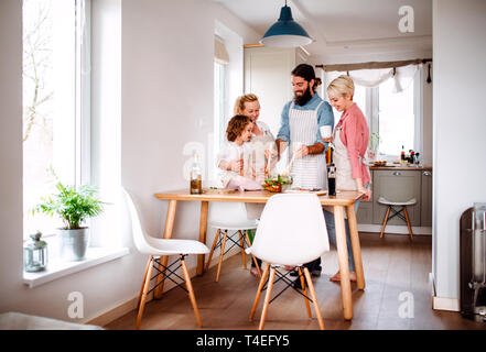 A portrait of small girl with parents and grandmother at home, preparing vegetable salad. - Stock Image