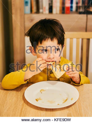 Young boy eating a waffle by a wooden table in a Polish house - Stock Image