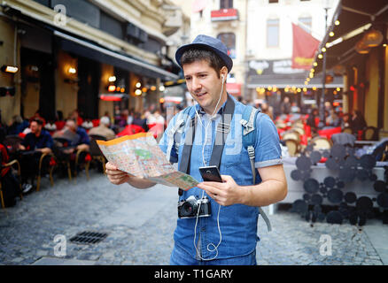 Backpacker Traveler Man traveling alone on crowded streets in old town. Neck camera and holding city map in hand. Travel Europe - Stock Image