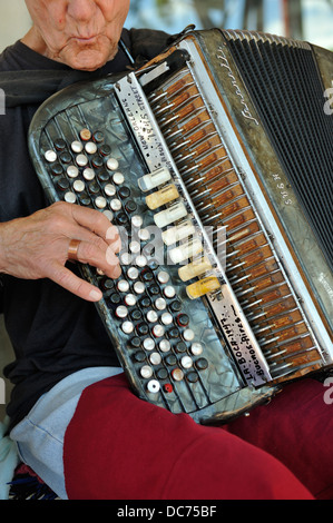 elderly busker playing old, battered Serenelli accordion - Stock Image