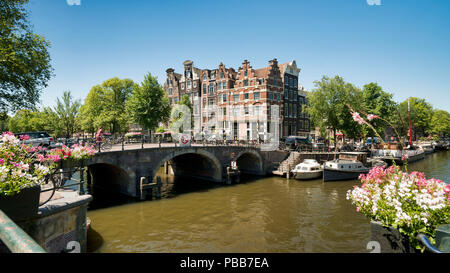 Sloop boat nearby crooked canal houses at Brouwersgracht, Amsterdam, The Netherlands - Stock Image