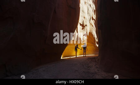 Rear view of silhouette of boyfriend and girlfriend exploring cave in scenic rock formations - Stock Image