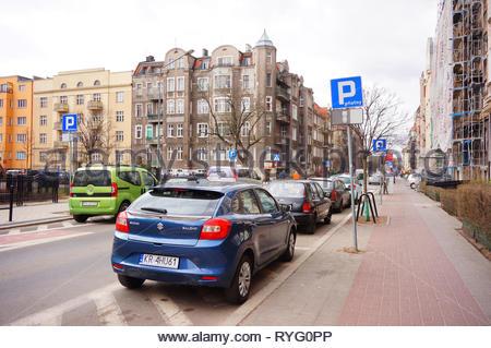 Poznan, Poland - March 8, 2019: Parked blue Suzuki Baleno car false parking by a sidewalk on the Slowackiego street in the city center. - Stock Image