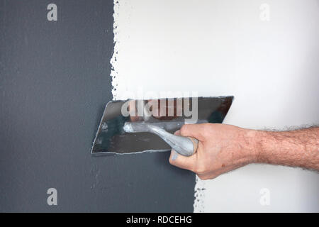 Hand with a trowel plastering a wall with decorative plaster - Stock Image