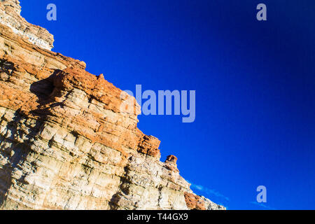 Red and orange geological rock formations in the desert. - Stock Image