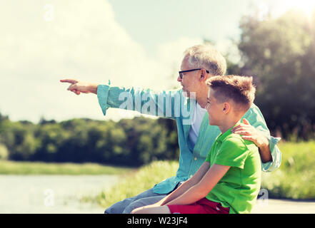 grandfather and grandson sitting on river berth - Stock Image
