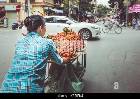 A street vendor pushes her produce through the busy streets of Hanoi's Old Quarter - Stock Image