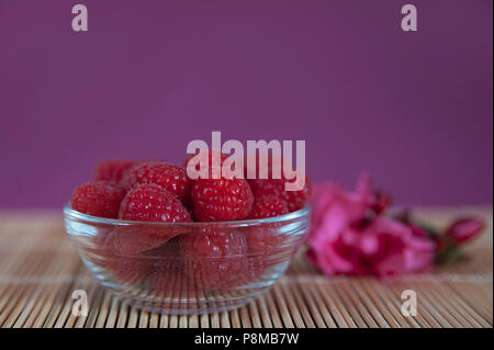 Horizontal shot of a bowl of raspberries freshly picked and positioned on a bamboo mat, with an out of focus ornamental flower and magenta background - Stock Image