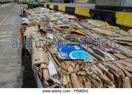 Bales of compacted cardboard ready for collection and recycling beneath a UK shopping mall - Stock Image
