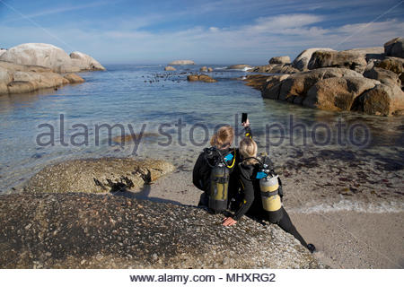 Couple in wetsuits going ocean scuba diving from rocky beach and taking selfie - Stock Image