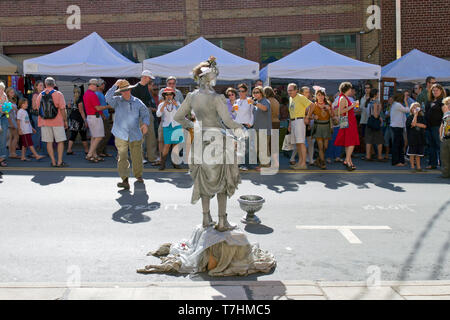 ASHEVILLE, NORTH CAROLINA, USA – 9/5/2010: A popular human statue busker known as the Silver Drummer Girl entertains crowds in the street as she holds - Stock Image