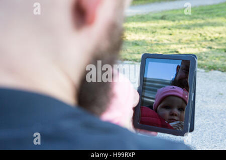 Father with baby girl in baby carrier using digital tablet - Stock Image