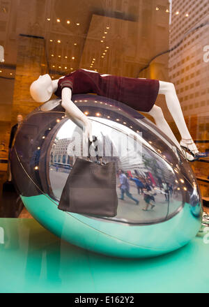 Manhattan, New York, U.S. - May 21, 2014 - In the Fendi 5th Avenue store window display, a manniquin wearing a brown dress and shoes is in supine position draped over a large structure resembling a silver Mylar balloon. A brown leather Fendi purse hangs from one hand. - Stock Image