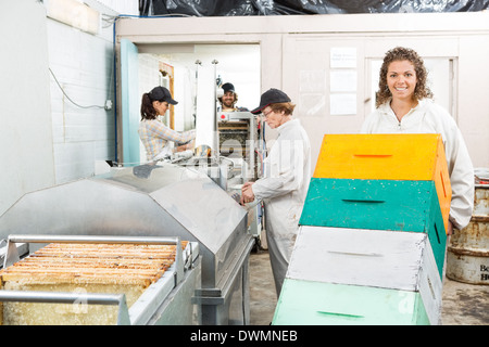 Female Beekeeper Holding Trolley Of Stacked Honeycomb Crates - Stock Image
