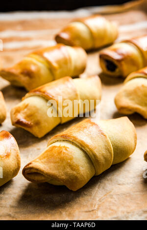 Freshly baked french pastry croissants or rolls on baking tray. - Stock Image