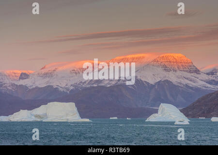 Greenland, Scoresby Sund, Gasefjord. Sunrise on the mountains with icebergs. - Stock Image