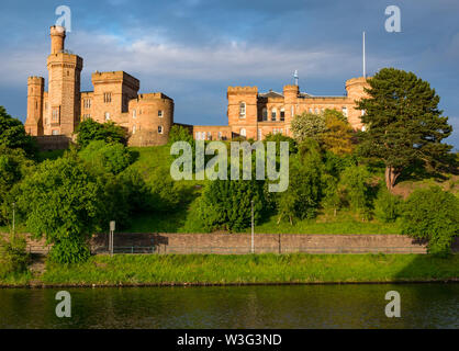 View across River Ness to sunlit  Inverness Castle on hilltop, Inverness, Scotland, UK - Stock Image
