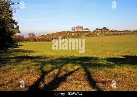 A view across farmland from a public footpath towards a house on a hill on Blakeney Downs, Norfolk, England, United Kingdom, Europe. - Stock Image