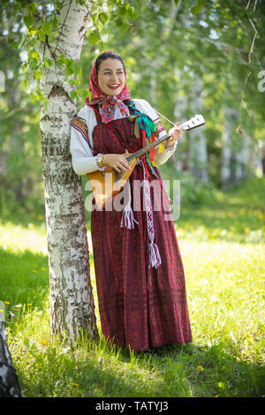 Smiling young woman in traditional russian clothes standing in the forest and playing balalaika, vertical shot - Stock Image