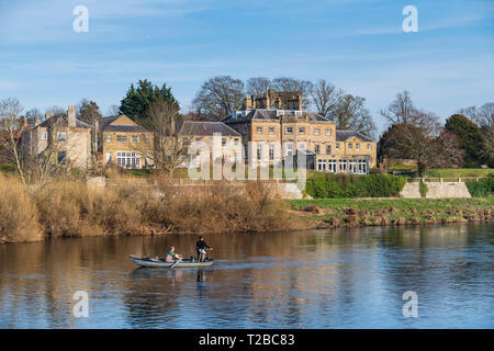 Ednam House Hotel and fishing boat on the Tweed river in Kelso, Scottish Borders, late February. - Stock Image