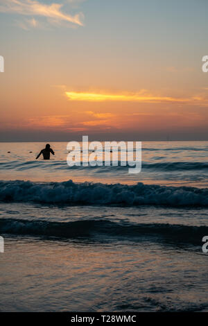 A man taking bath at beach during sunset - Stock Image