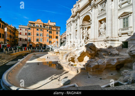 An art historian cleans and maintains the empty, drained Trevi Fountain on a sunny afternoon in early autumn in Rome, Italy - Stock Image