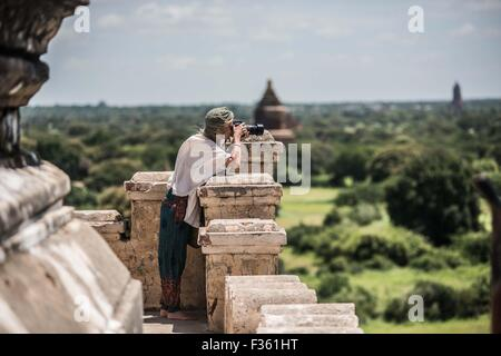A traveler takes pictures of temples in Bagan, Myanmar - Stock Image