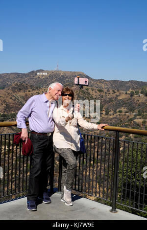Senior couple taking selfie photograph with cell phone in front of Hollywood sign at Griffith Park Observatory Los - Stock Image