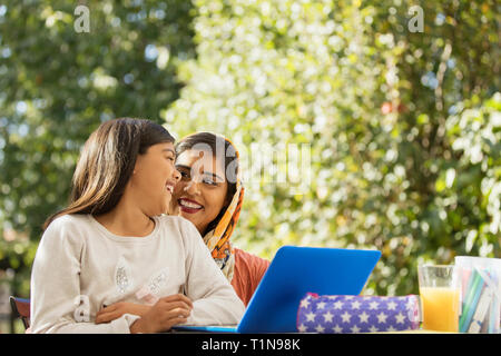 Happy mother and daughter using laptop on patio - Stock Image